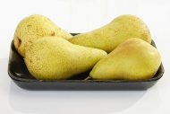 Four yellow pears on a plasti...