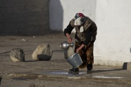 Kirghiz woman washing tin buc...