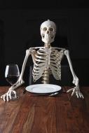 Skeleton sitting at a laid ta...
