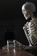 Skeleton holding a glass of w...