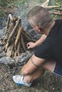 Man lighting a fire on a meadow