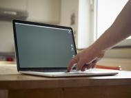 Laptop on kitchen table, hand...