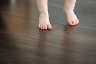Feet of baby girl on dark floor