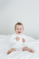 Smiling baby girl sitting on bed