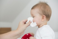 Mother blowing baby girl\'s nose