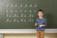 Schoolboy at blackboard writi...