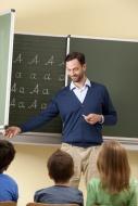 Teacher at blackboard with va...