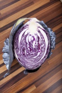 Half of a red cabbage on wood