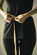 Mid-adult woman measuring waist