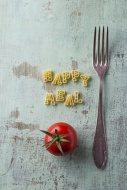 Pasta letters, tomato and a fork