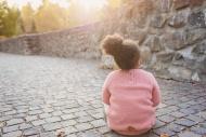 Little girl sitting on walkway