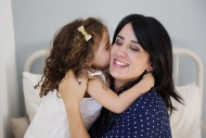 Daughter kissing mother on th...