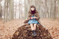 Young girl sitting on autum l...