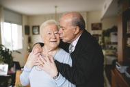 Senior couple hugging and kis...