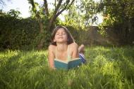 Happy girl lying on meadow wi...