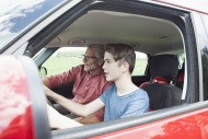 Father teaching son driving a...
