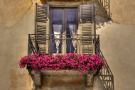 Old balcony with red flowers ...