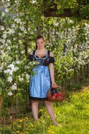 Woman in dirndl stands beside...