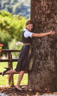 Girl in dirndl on a tree