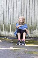 Girl (10) sitting on skateboa...