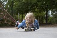 Girl (10) lies on skateboard,...