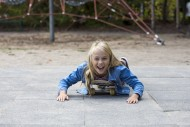 Girl (10) lies on skateboard,...