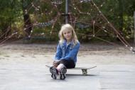 Girl (10) sits on skateboard,...