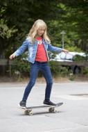 Girl (10) stands on a skatebo...