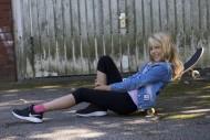 Girl (10) lies on a skateboar...