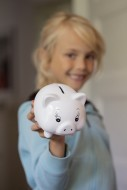 Girl (7) with piggy bank, Kie...